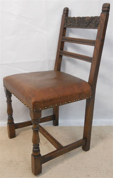 set of four carved oak tudor style leather seat dining