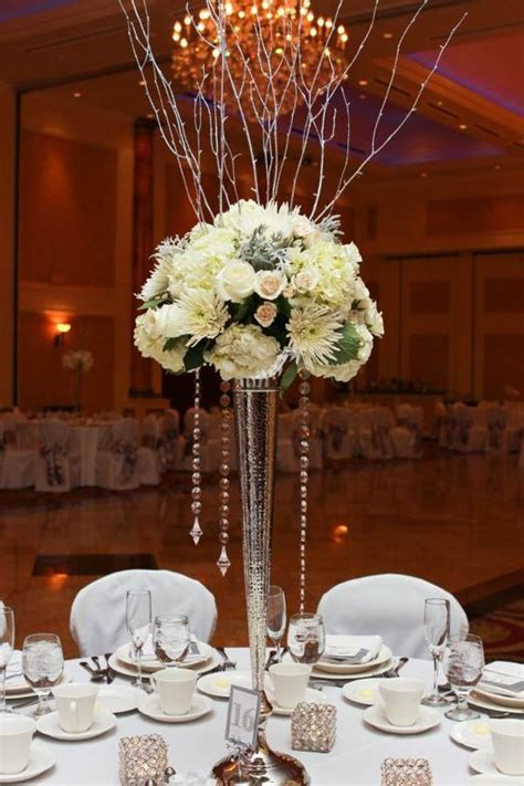 winter wedding centerpiece on tall silver vase with silver