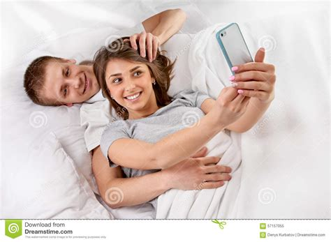 fun in bed couple in bed taking a picture with smartphone stock photo