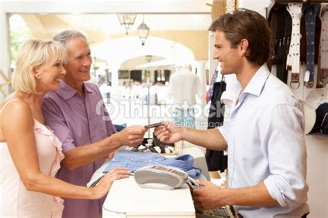 male sales assistant at checkout of clothing store with