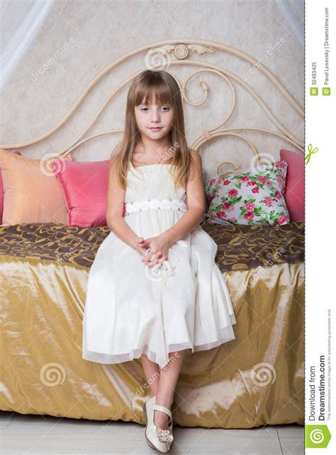 girl sitting on bed little girl sitting on the bed royalty free stock photo image 32483425