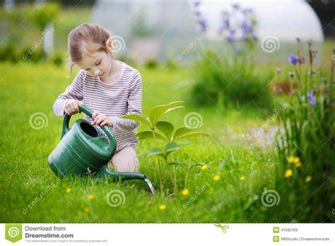 girl watering flowers cute little girl watering plants in garden stock photo