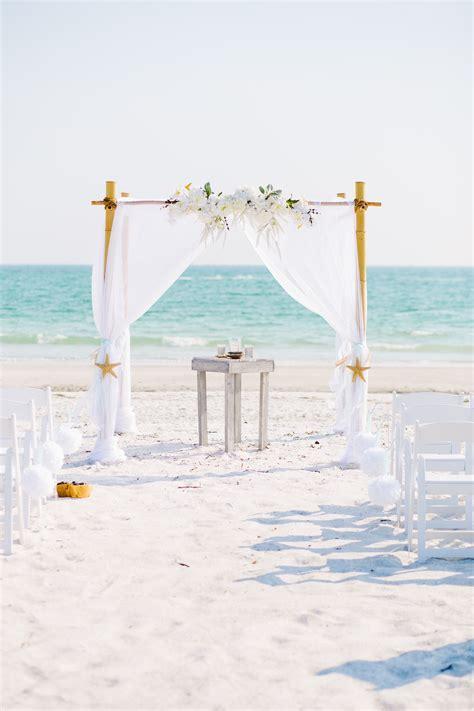 Elegant white beach wedding arbor.   Wedding in 2019