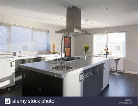 modern kitchen island with hob sink and breakfast extractor fan above central island unit with set in hob