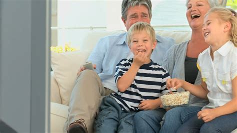 family watching tv with popcorn in living room stock photo family watching tv while eating popcorn in the living room