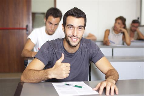 hipster male student showing thumb group stock photo good looking young student in class with thumb up stock