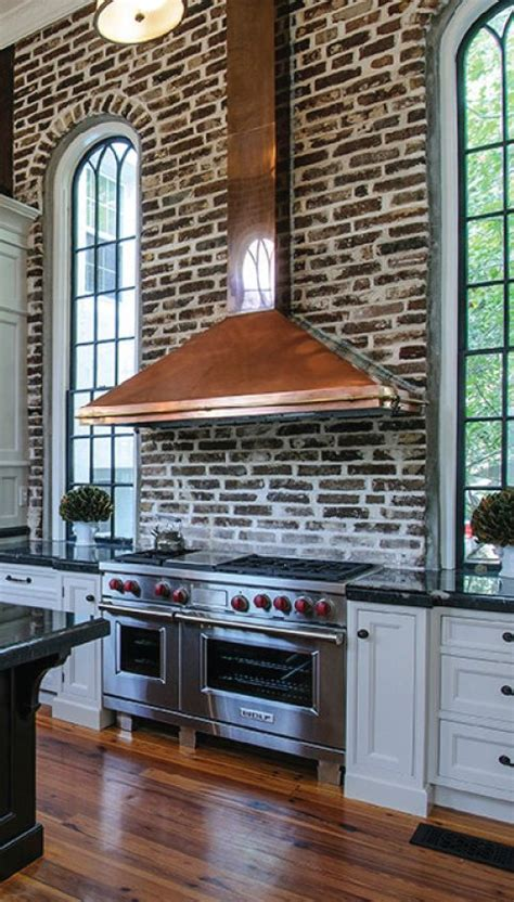 brick backsplash and copper hood would look great with exposed brick kitchen backsplash with brass stove hood
