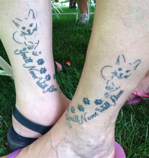 alone tattoo you will never walk alone cat and paw prints tatoos on legs