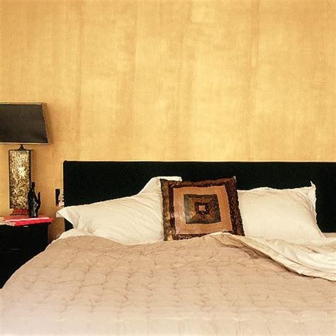 gold paint bedroom ideas bedroom with gold wall black headboard and fifties ls