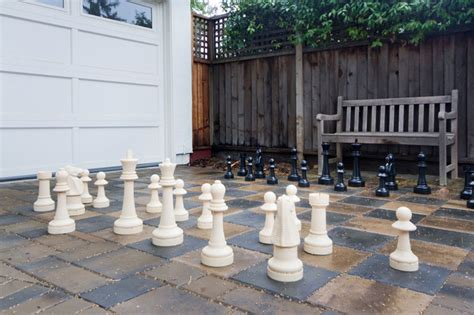 outdoor chess set on paver driveway
