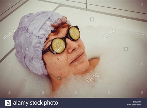 mature woman in bathtub with cucumber slices on glasses