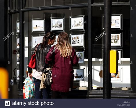 buy the house estate agents a couple of women studying the house price signs in an estate agents stock photo
