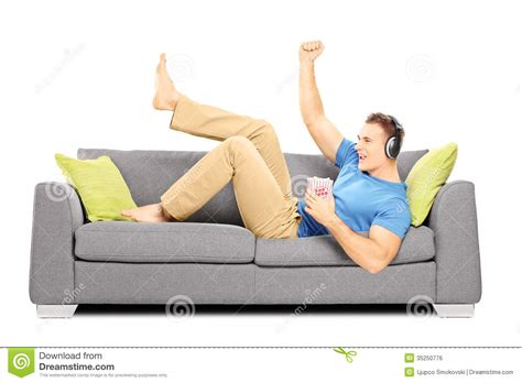 lie on the couch excited guy lying on a sofa and listening music royalty
