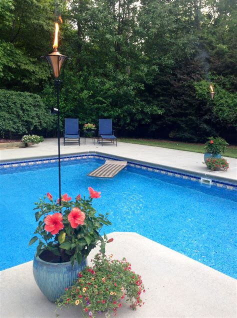 poolside landscaping tiki torches in the flowers around the pool inground