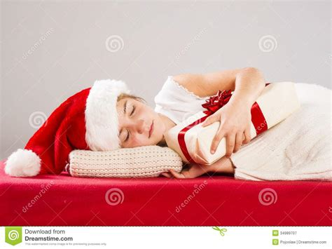 hat on the bed small girl in santa hat with christmas gift royalty free