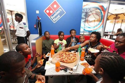 domino pizza lagos a family eats domino s pizza at a restaurant in lagos