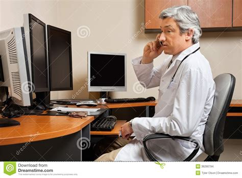 doctor attending phone call at clinic stock photo image