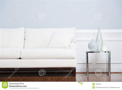 sofa table against wall white sofa and glass end table against blue wall stock
