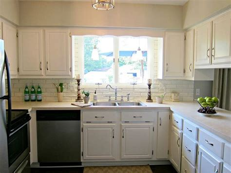 kitchen white cabinets beige countertop grey green paint white brick backsplash pendant