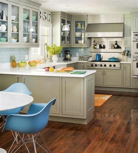 gray and blue kitchen with taupe cabinets paired with white countertops and blue subway tile