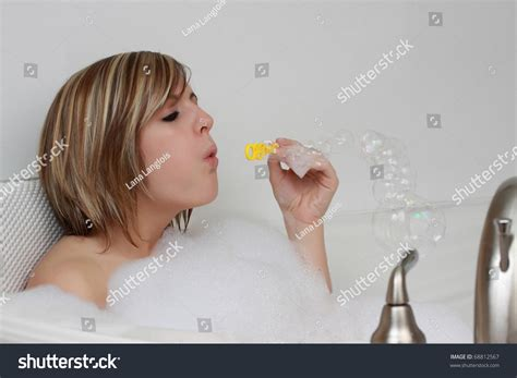 bathtub bubble soap young caucasian woman blowing soap bubble in her bath