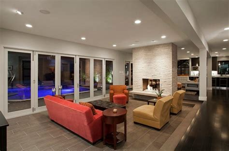 awesome Wall Designs For Living Room #3: sunken-living-room-with-banquette-style-seating-and-fireplace-wall-divider-also-glass-bi-fold-retractable-door-connected-to-the-pool-outside-718x474.jpg