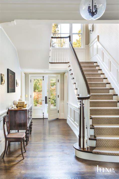 white foyer  antique pieces  staircasedesigner