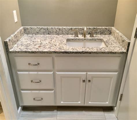 "Ashen white granite countertops, Moen 8"" widespread faucet"