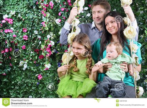 garden for family of 4 happy family on swing look toward near hedge stock photo