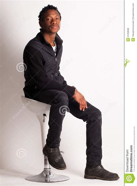 White Sitting Chair by Handsome Black Sitting On A Chair Stock Photo Image