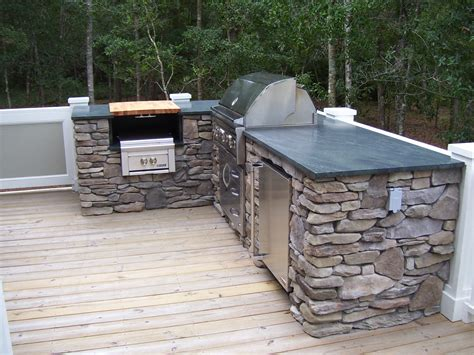 the outdoor kitchen soapstone countertop matches the kitchen countertop indoors all equipment