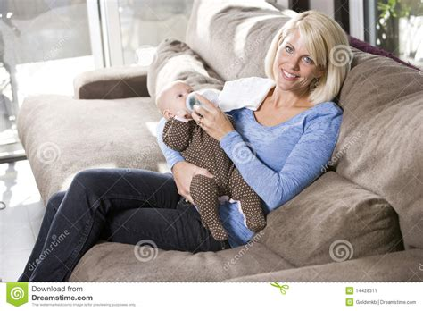 mom couch mom feeding bottle to baby at home on couch stock image