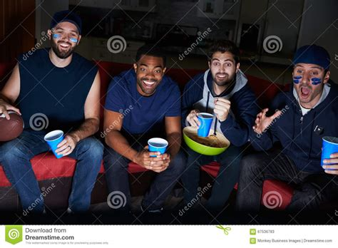 type of sport that fans watch on tv on thanksgiving group of male sports fans watching game on television