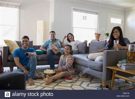 family watching tv with popcorn in living room stock photo father son watching tv in stock photos father son