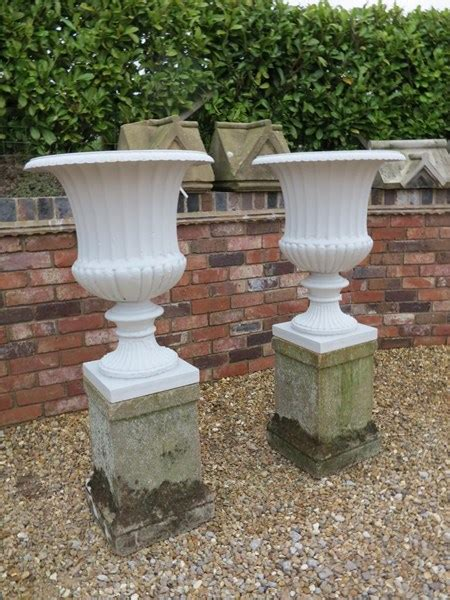 pair  cast iron planters  reconstituted stone plinths