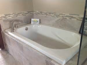 drop in tub with gray tile bathroom