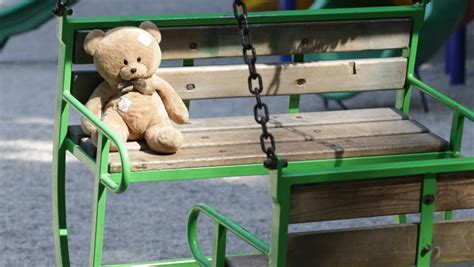 teddy plays on the swing nap teddy bear toy swinging in a swing at playground in