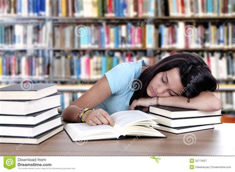 Student Sleeping On Desk by Tired Student Sleeping At The Desk In A Library Royalty