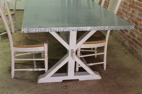Zinc trestle table seen with matching fanback chairs