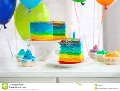 rainbow cake and cupcakes decorated with birthday candles rainbow cake decorated with birthday candle stock photo image 50083878