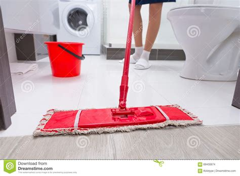mopping bathroom floor housewife mopping the floor in a bathroom stock photo