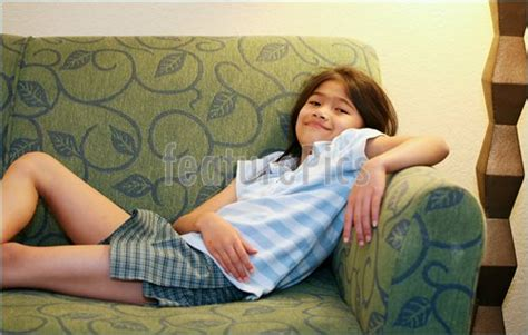 little couch photo of little girl relaxing on couch