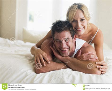lying or laying in bed couple lying in bed smiling royalty free stock photography