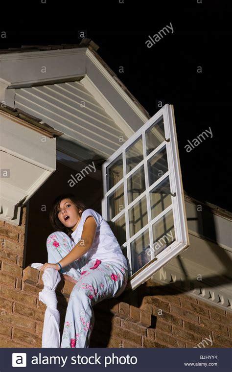 her bedroom window teenager climbing out of her bedroom window stock photo