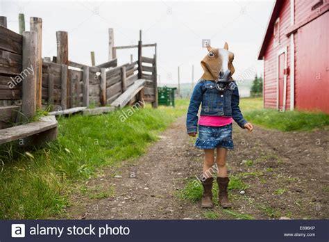 girl wearing horse head mask girl wearing horse mask outside barn stock photo royalty