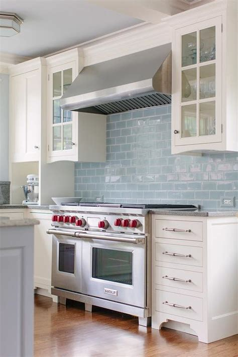 light blue kitchen backsplash white kitchen cabinets with black and gray granite countertops transitional kitchen