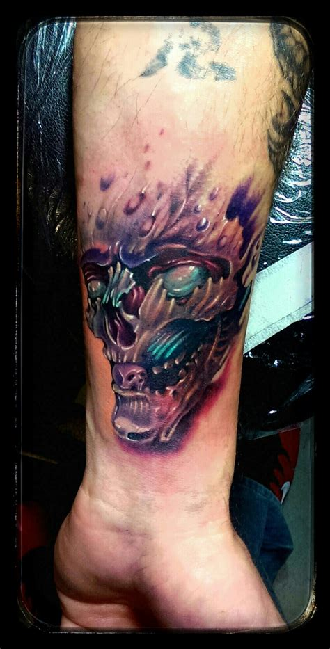 tattoos with color colored skull on left forearm