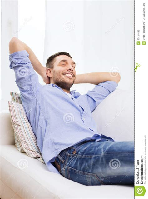 people having on the couch smiling man relaxing on couch at home stock photo image
