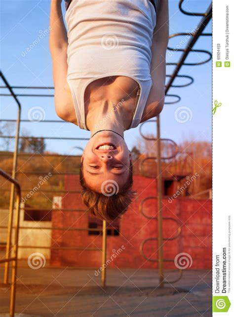 teen girl hanging upside down girl hanging upside down on gymnastics rings stock image