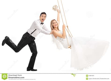 pushing a swing man pushing his newlywed wife on a swing stock photo